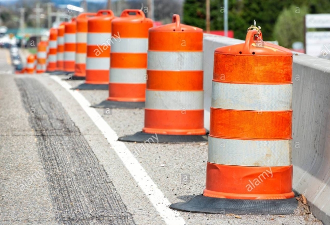 orange traffic-barrels-down-the-side-of-a-road-with-shallow-depth-of-field-T2EJ4Y
